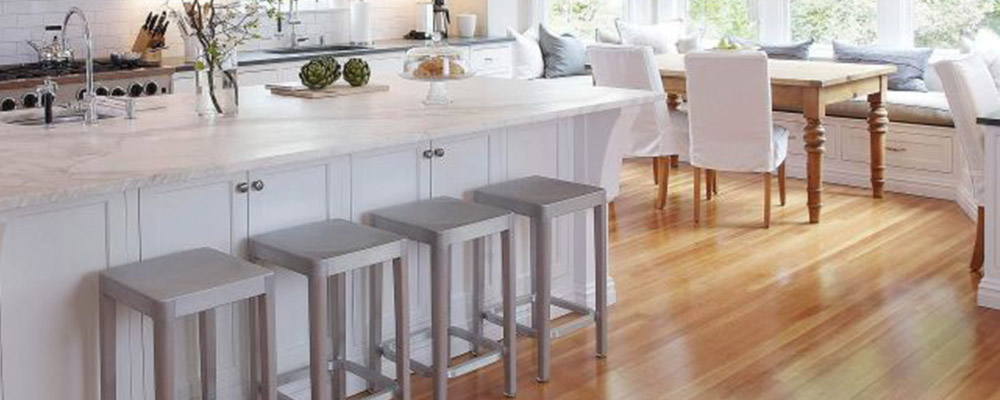 Light brown hardwood flooring. White cabinets. Grey stools.