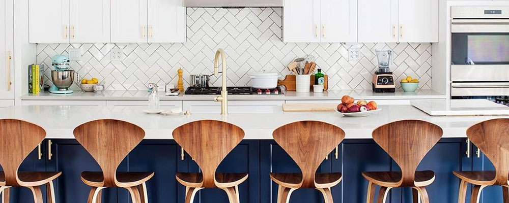 Navy blue island. White cabinets. Wood stools.