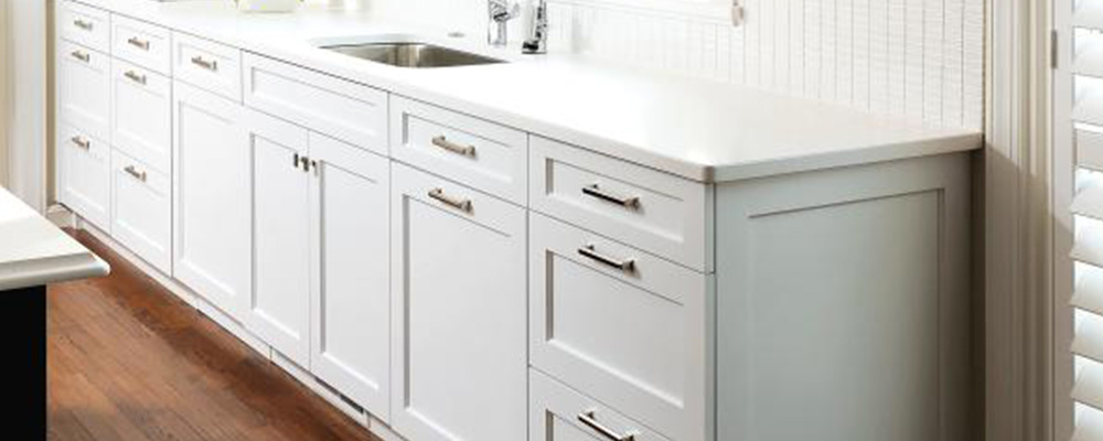 White kitchen with white countertop and silver handles