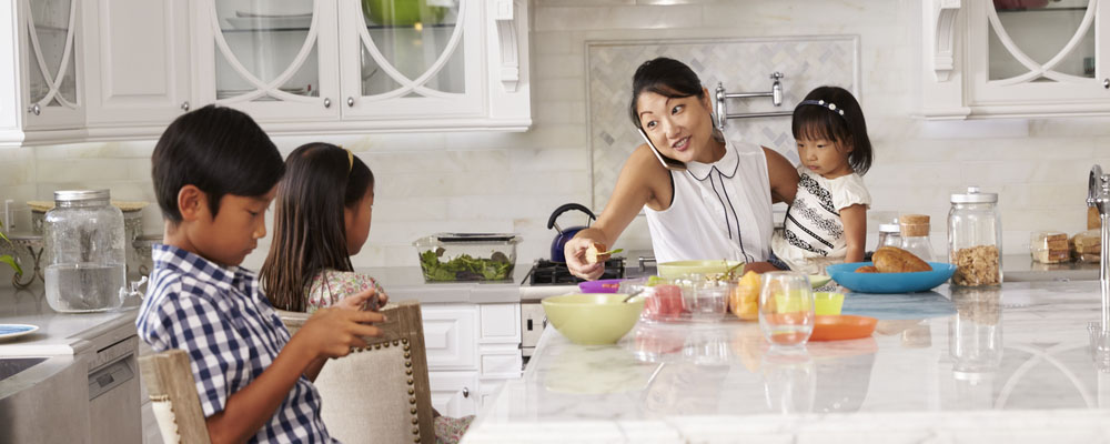 A photo of a children sitting down around the kitchen table, while the mother is preparing breakfast. Kitchen Organizational Tips