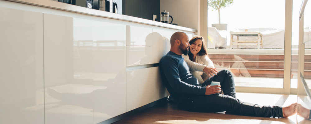 A photo of a couple sitting down on there kitchen floor and enjoying their newly organized kitchen. Kitchen Organizational Tips.