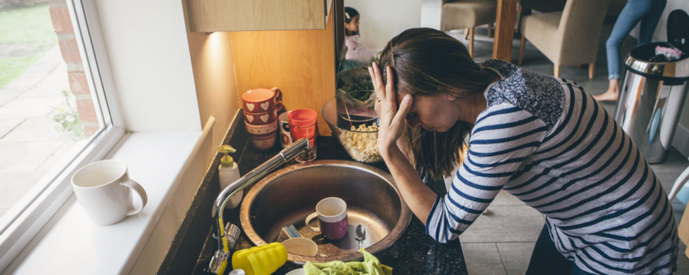 A photo of a woman with her head down and stressed over her cluttered kitchen. Kitchen Organizational Tips.